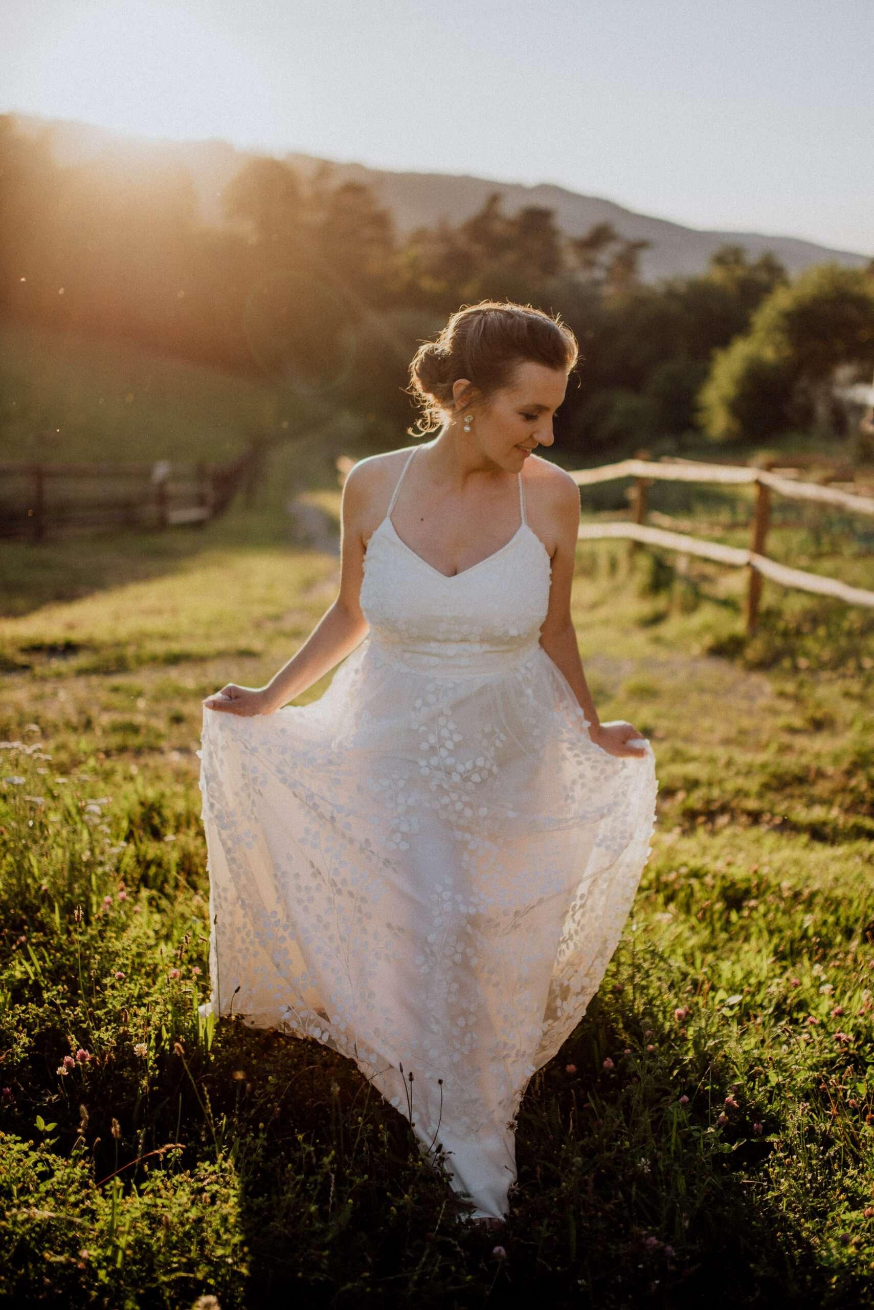 Nevěsta ve svatebních šatech jde po louce při západu slunce