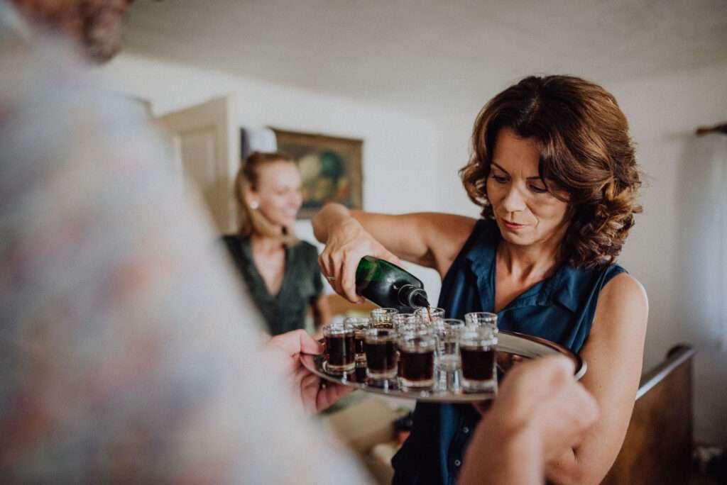 Svatební hosté rozlévají panáky alkoholu během příprav nevěsty