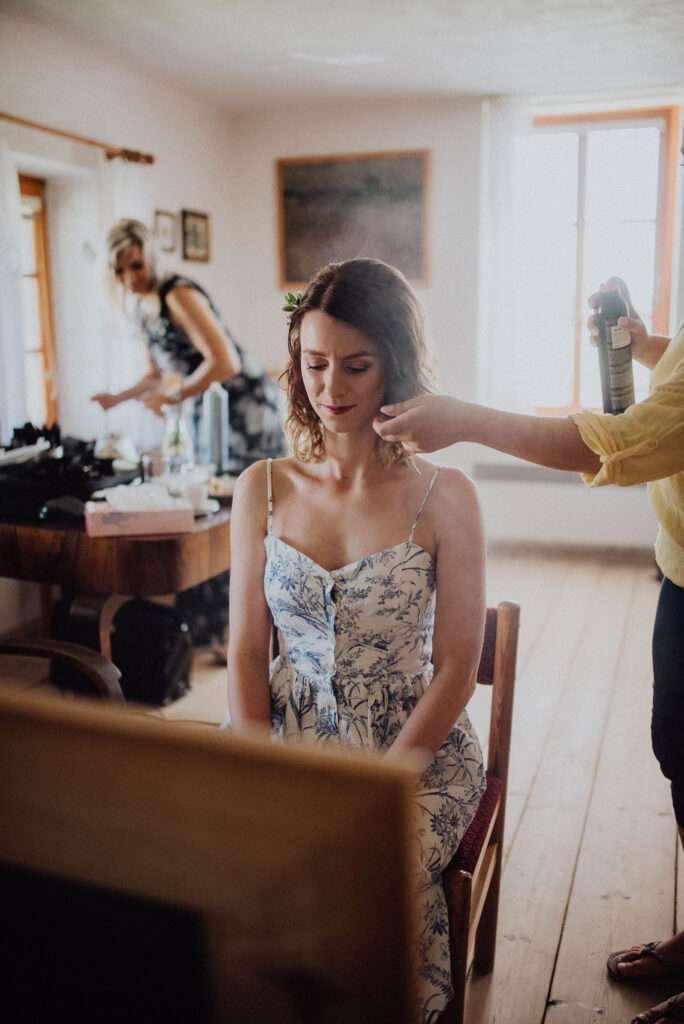 Nevěsta si nechává připravit účes před svatebním obřadem