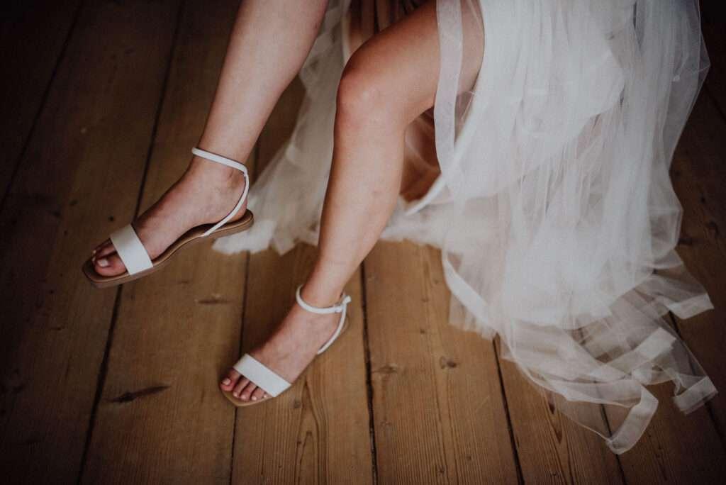 Nevěsta si v rustikální místnosti nazouvá svatební boty