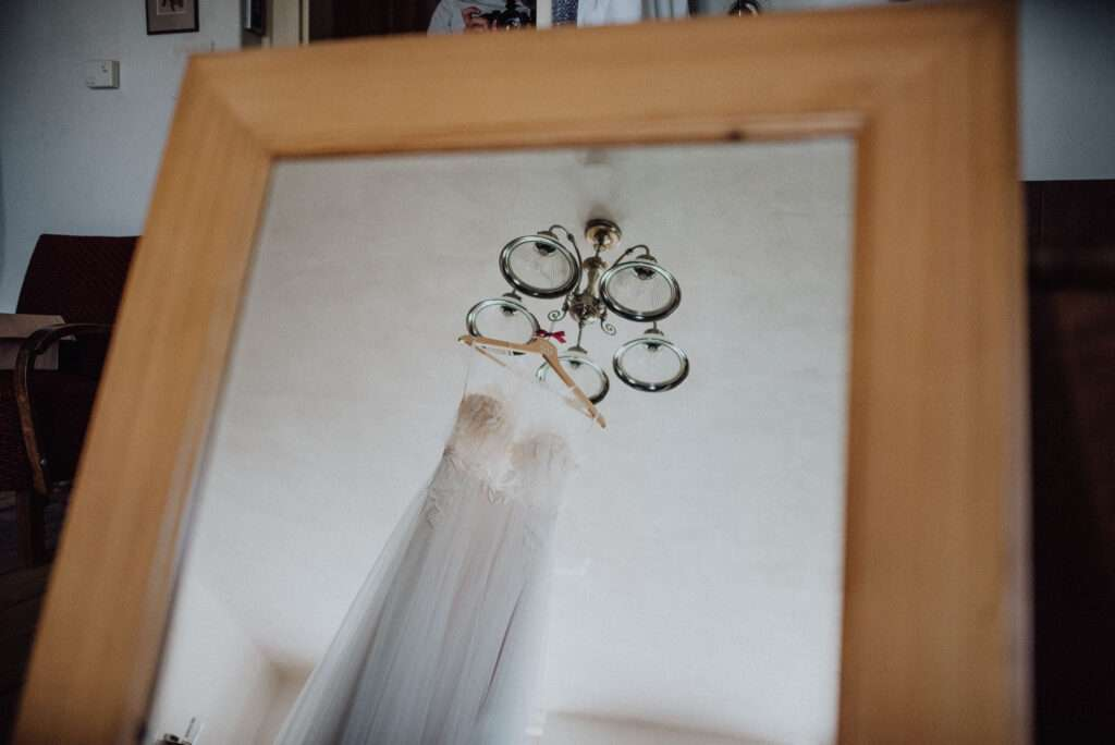 Svatební šaty pověšené na lustru během příprav nevěsty