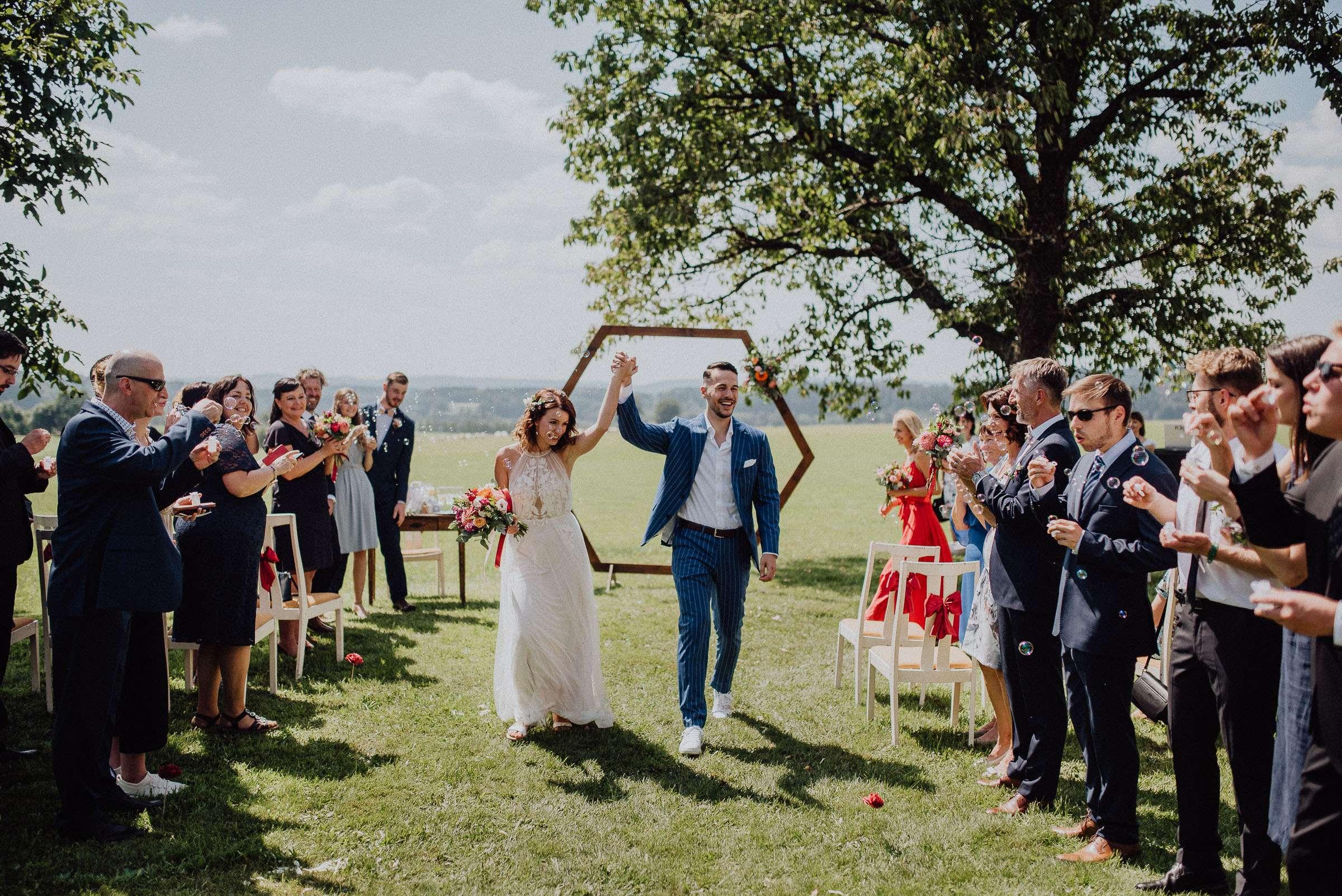 Ženich s nevěstou odchází po obřadu špalírem na svatbě Orlické hory