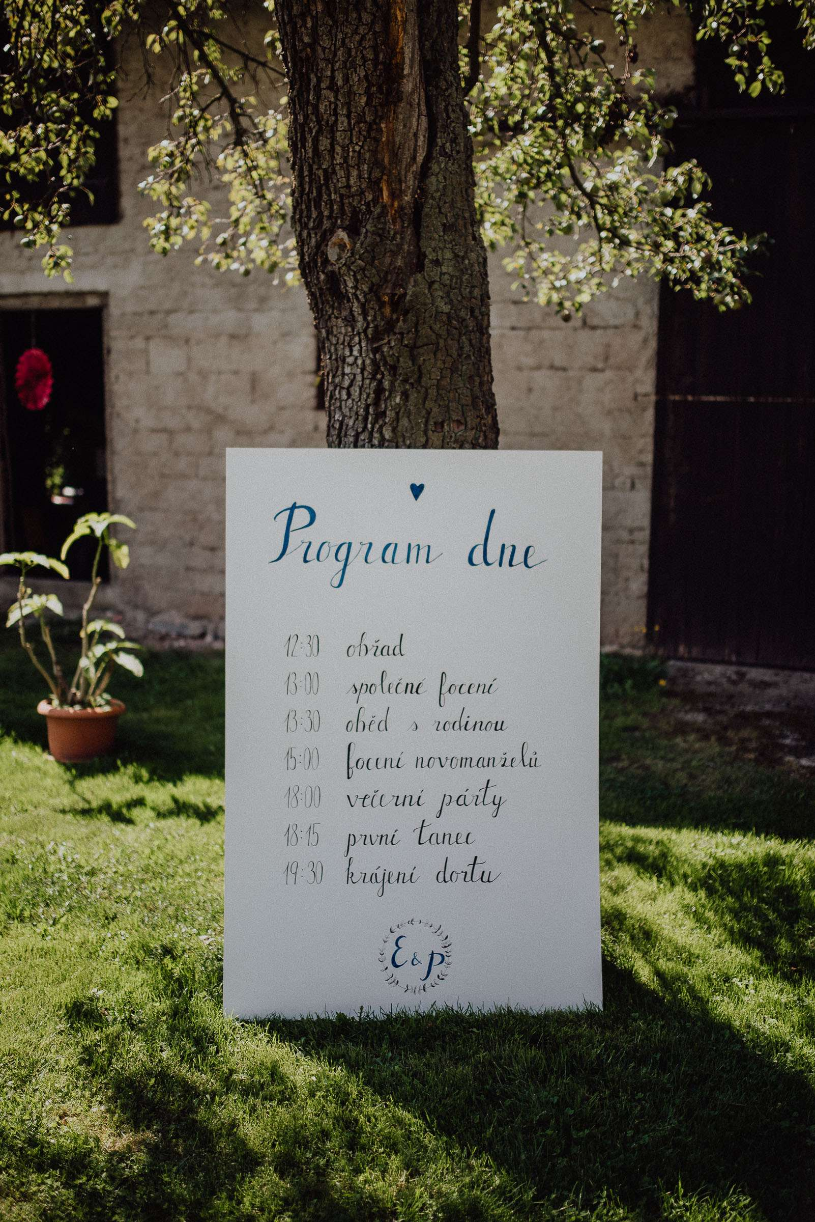 Cedule s programem svatby opřená o strom vedle stodoly