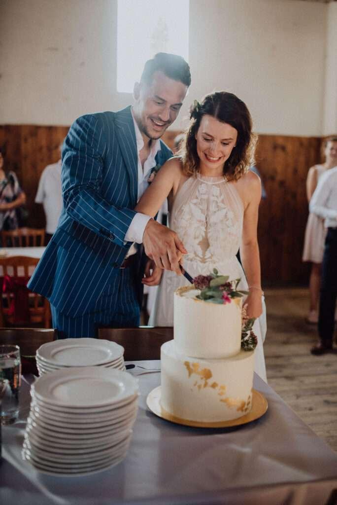 Krájení dortu uprostřed rustikální stodoly