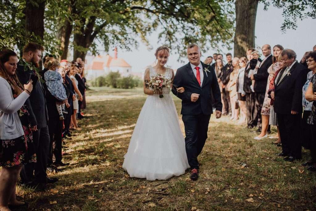 Nevěsta jde uličkou za ženichem v sadu pod stromy