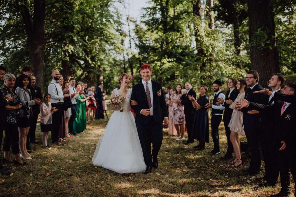 Novomanželé odchází za potlesku špalírem pod stromy v sadu