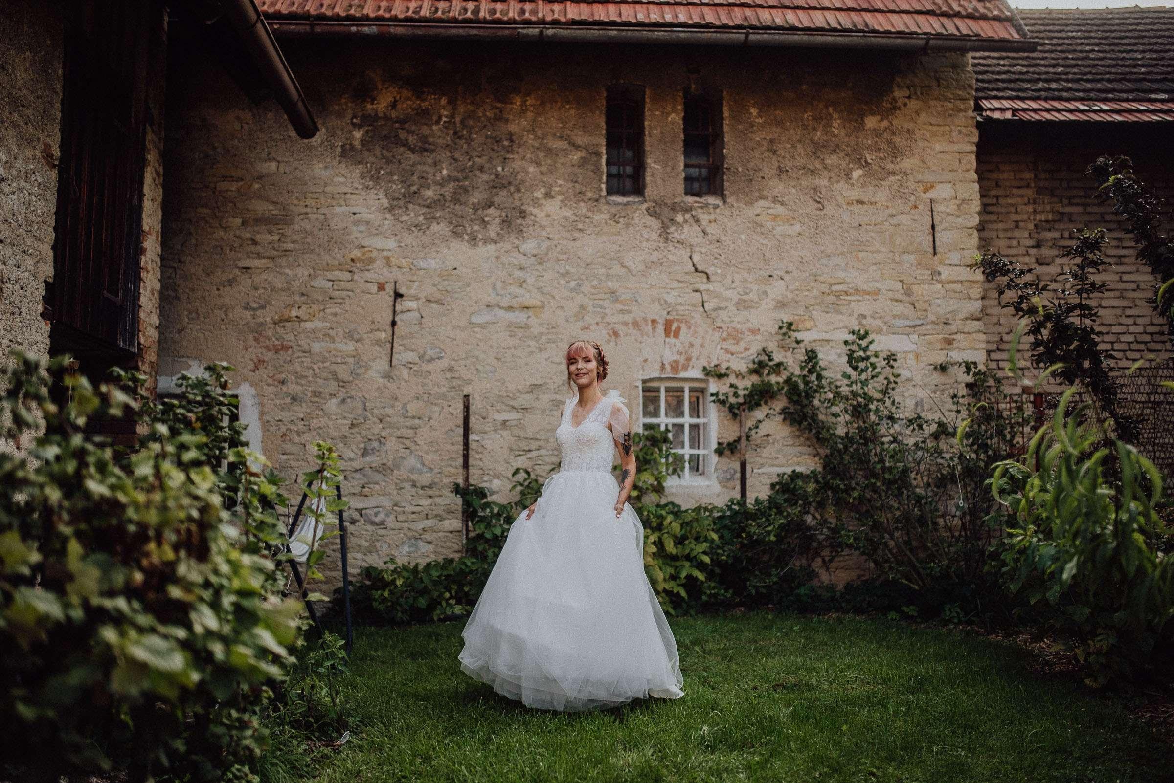 Portrét nevěsty ve svatebních šatech v rustikální zahradě
