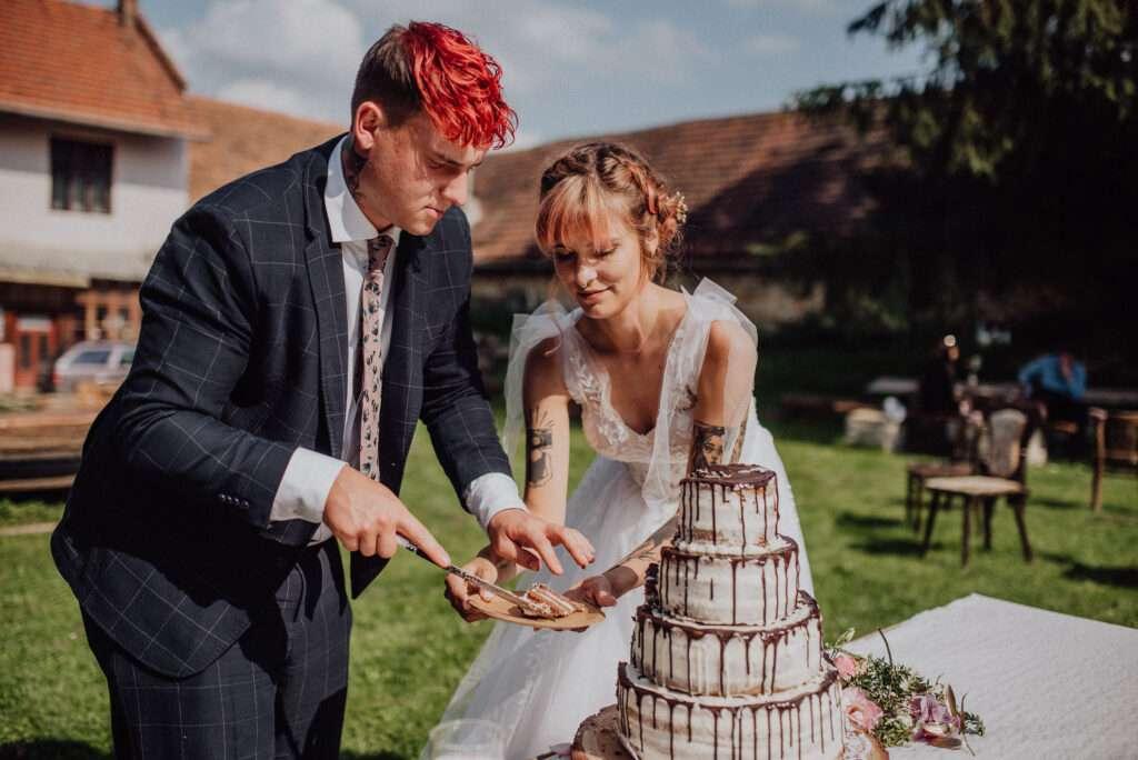 Ženich s nevěstou krájí svatební dort