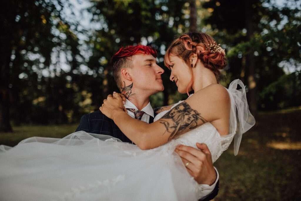 Ženich nese nevěstu v náručí sadem