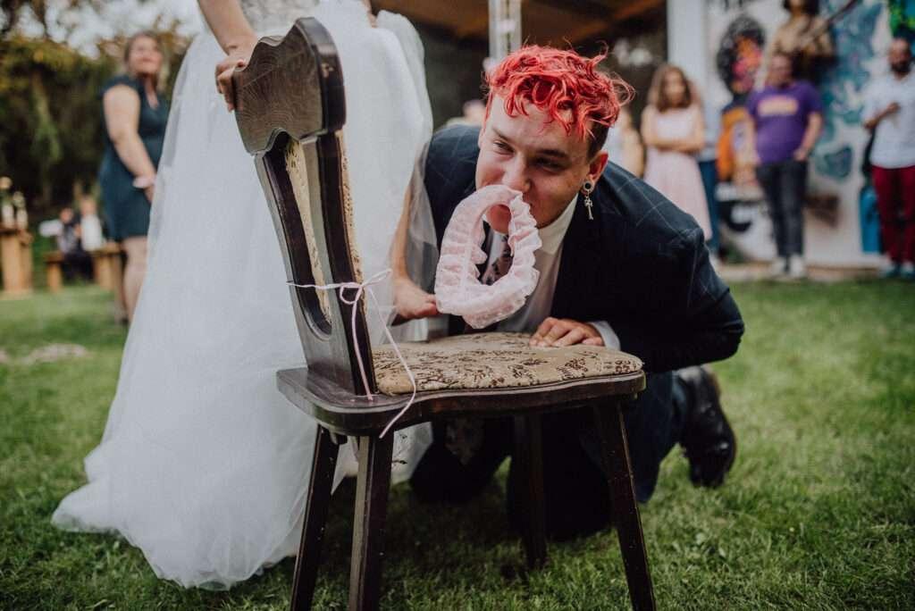 Ženich drží v zubech podvazek nevěsty