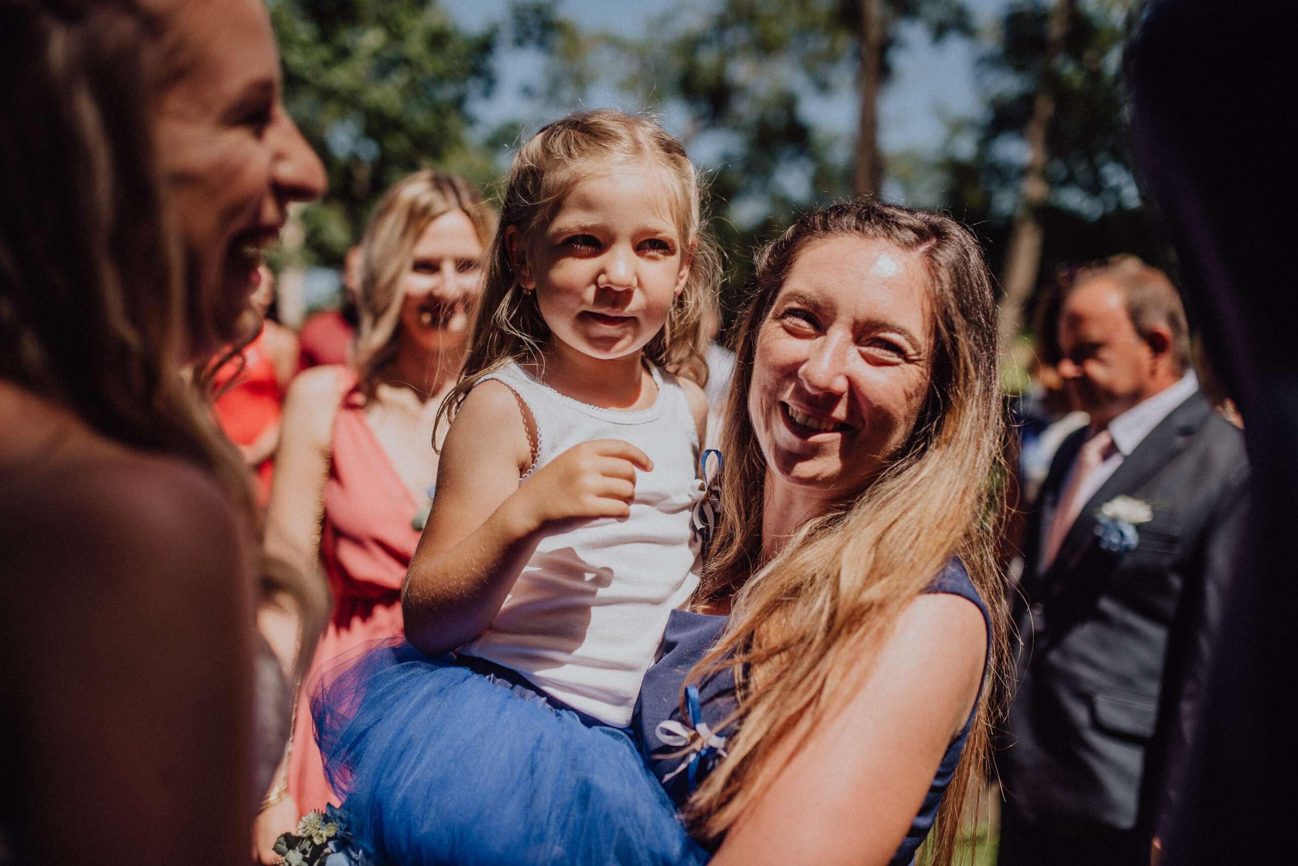 Žena s dítetem na svatbě v ostrém poledním slunci